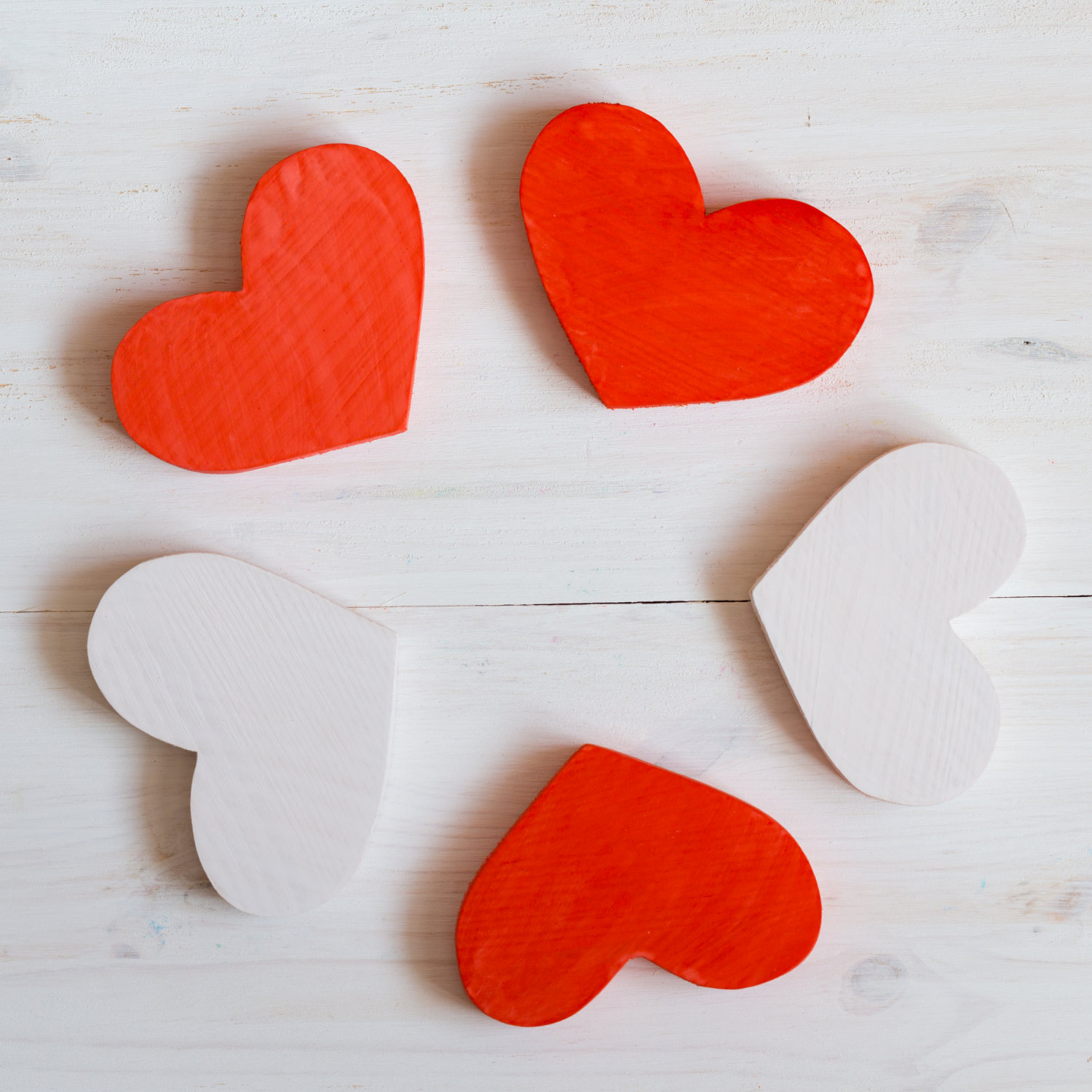 red-and-white-hearts-on-white-wooden-background-PZS9JZN.jpg
